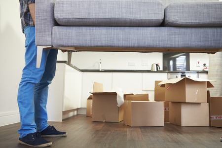 man carrying box: Close Up Of Man Carrying Sofa As He Moves Into New Home