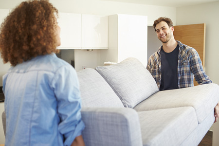 new home: Couple Carrying Sofa As They Move Into New Home