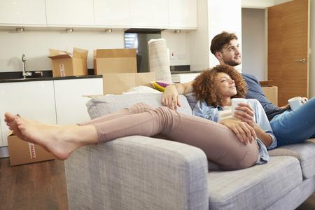 excitment: Pareja de relax en el sofá con la bebida caliente En Nuevo Hogar Foto de archivo