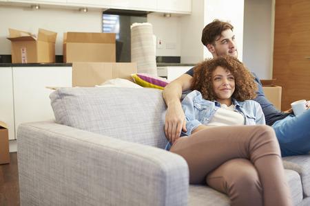 夫婦の新しい家で温かい飲み物が付いているソファーでリラックス 写真素材