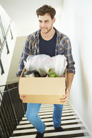 man carrying box: Man Moving Into New Home Carrying Box Upstairs