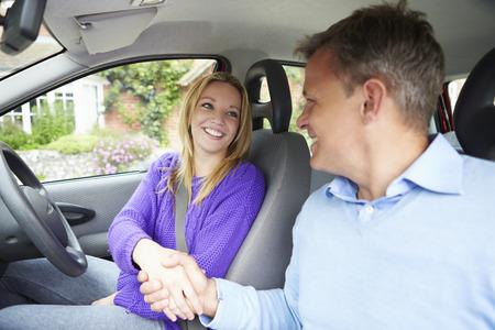 Teenage Girl Passing Driving Test Met Examiner Stockfoto