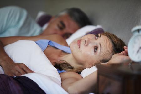 Paar in bed met vrouw lijden aan slapeloosheid Stockfoto