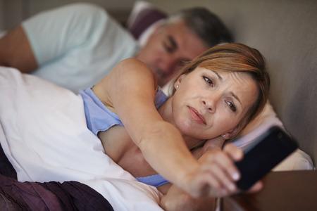despertarse: Pares en cama con la esposa sufre de insomnio Foto de archivo