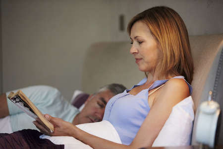 Middle Aged Couple In Bed Together With Woman Reading Book photo