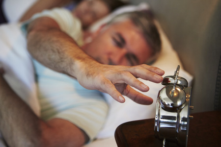early 50s: Couple In Bed With Man Reaching To Switch Off Alarm Clock