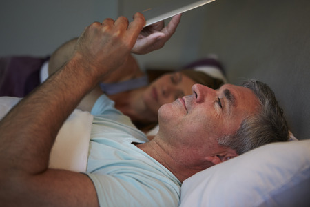 Middle Aged Couple In Bed With Man Using Tablet Computer photo