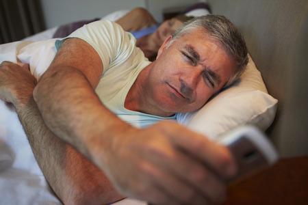 不眠症を患っている夫と一緒にベッドでカップル 写真素材