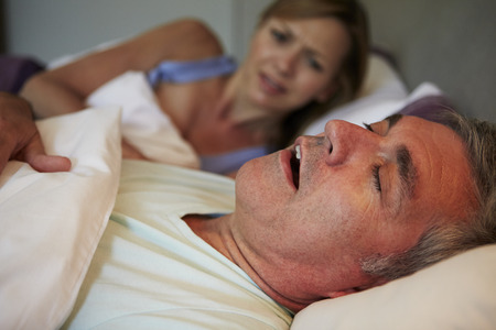 annoyed: Man Keeping Woman Awake In Bed With Snoring Stock Photo