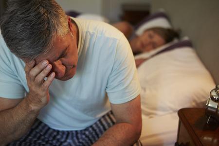 insomnio: El hombre despierta en la cama que sufre con el insomnio