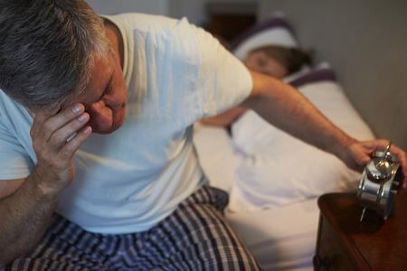 hombre preocupado: El hombre despierta en la cama que sufre con el insomnio