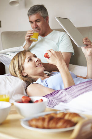 eating breakfast: Couple Eating Breakfast In Bed With Paper And Digital Tablet