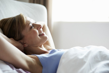 wake up happy: Attractive Middle Aged Woman Waking Up In Bed
