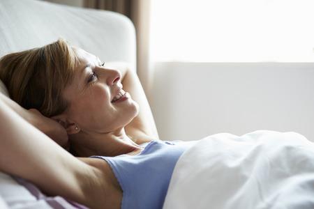 despertarse: Envejecida media atractiva Mujer que despierta en la cama Foto de archivo