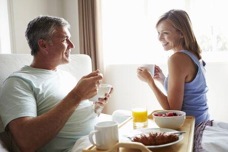 eating breakfast: Wife Bringing Husband Breakfast In Bed On Tray