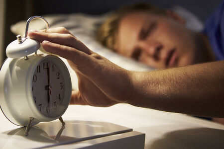 Teenage Boy Waking Up In Bed And Turning Off Alarm Clock Zdjęcie Seryjne