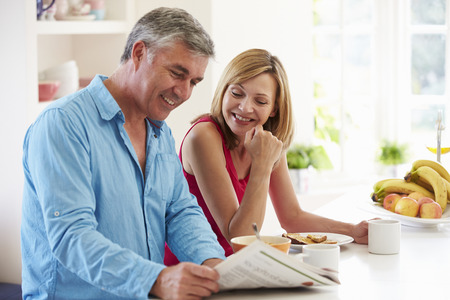 Middle Aged Couple Having Breakfast In Kitchen Together Stock Photo