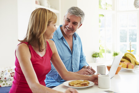 breakfast cereal: Couple Using Laptop Whilst Having Breakfast In Kitchen Stock Photo