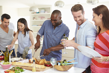 preparing food: Group Of Friends Having Dinner Party At Home Stock Photo