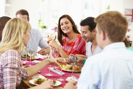 dinner party people: Group Of Friends Sitting Around Table Having Dinner Party Stock Photo