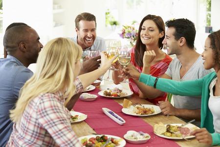 relajado: Grupo de amigos que hacen la tostada alrededor de la mesa en la cena de la fiesta