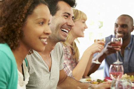 eat: Group Of Friends Sitting Around Table Having Dinner Party Stock Photo