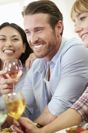 Vertical: Grupo de amigos que se sientan alrededor de la mesa Tener Dinner Party Foto de archivo