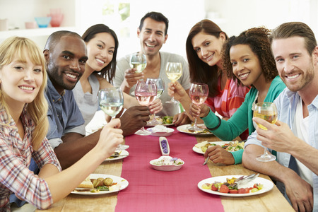 people   lifestyle: Group Of Friends Sitting Around Table Having Dinner Party Stock Photo