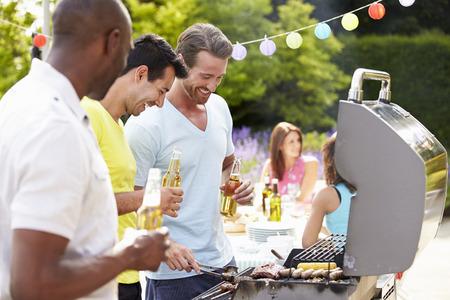 自宅でバーベキューで料理の男性のグループ