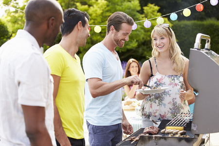 party table: Group Of Friends Having Outdoor Barbeque At Home Stock Photo