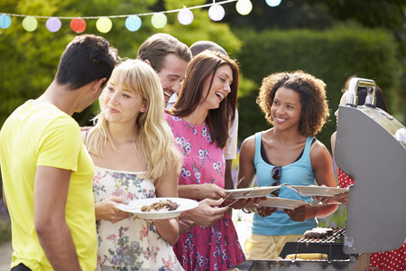 Group Of Friends Having Outdoor Barbeque At Home Standard-Bild