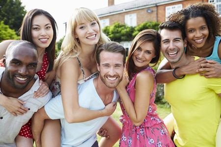 grupo de personas: Retrato de amigos se relajan en jard�n del verano junto