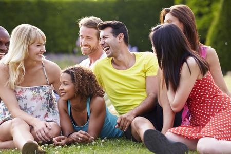 一緒に芝生の上に座っている友人のグループ