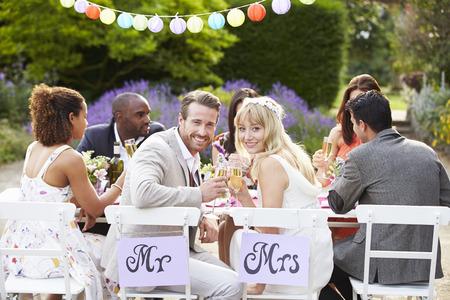花嫁と新郎の結婚披露宴での食事を楽しんで 写真素材