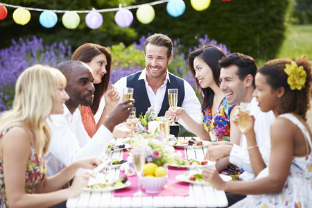 home garden: Group Of Friends Enjoying Outdoor Dinner Party Stock Photo