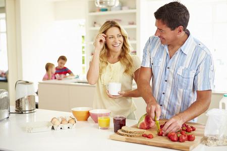 Ouders voorbereiden Familie Ontbijt in Keuken Stockfoto