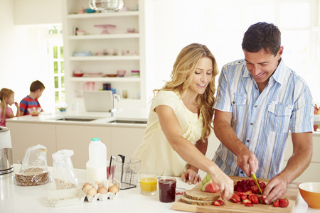Parents Preparing Family Breakfast In Kitchen photo
