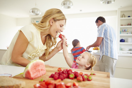 Daughter Helping Mother To Prepare Family Breakfast photo