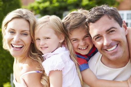 niñas sonriendo: Retrato de familia feliz en jardín