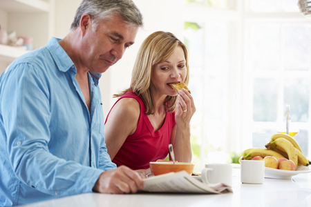 Middle Aged Couple Having Breakfast In Kitchen Together photo