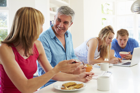 Teenage Family Having Breakfast In Kitchen With Laptop Stock Photo