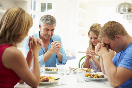 family praying: Family Saying Prayer Before Eating Meal At Home Together