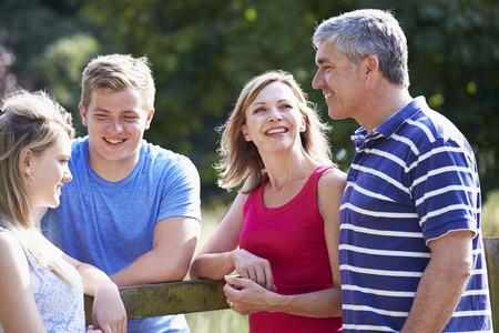 Familia con niños adolescentes que recorren en campo