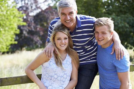 madre e hija adolescente: Padre con niños adolescentes que recorren en campo