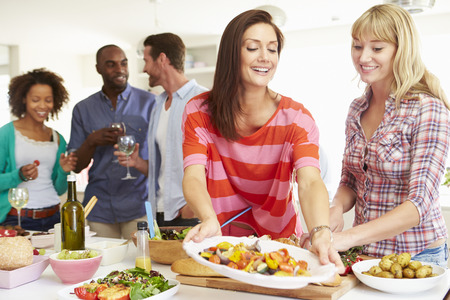 woman eat: Group Of Friends Having Dinner Party At Home Stock Photo
