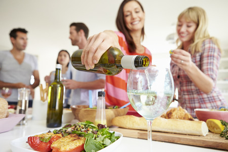 glass of white wine: Group Of Friends Having Dinner Party At Home Stock Photo