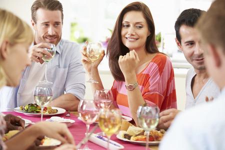 bebiendo vino: Grupo de amigos que se sientan alrededor de la mesa Tener Dinner Party Foto de archivo