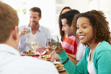 dinner party: Group Of Friends Sitting Around Table Having Dinner Party Stock Photo