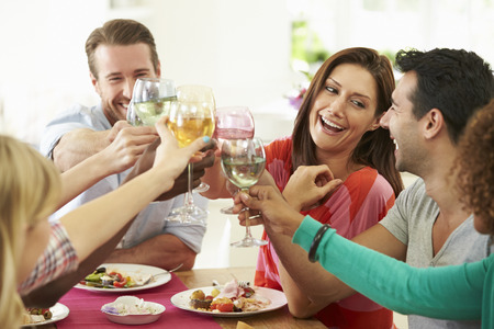 friend: Group Of Friends Making Toast Around Table At Dinner Party