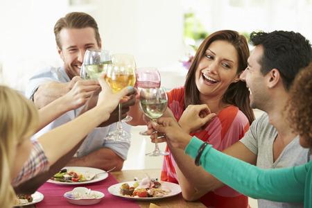 comidas: Grupo de amigos que hacen la tostada alrededor de la mesa en la cena de la fiesta